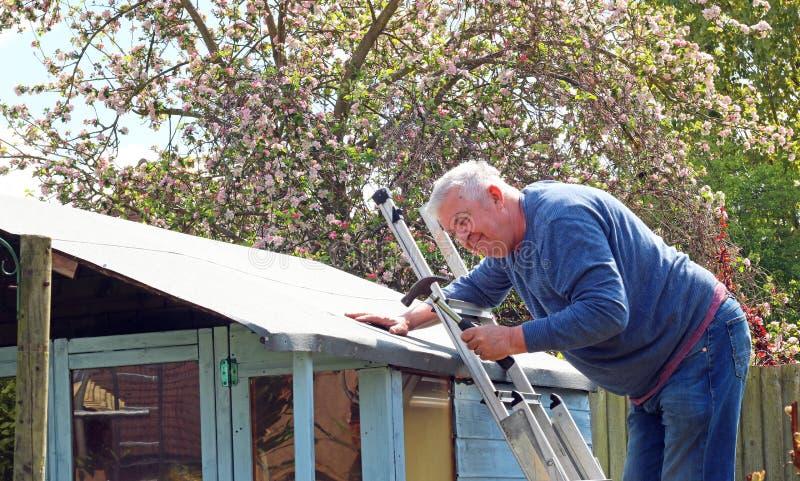 老人修理棚屋顶 免版税图库摄影