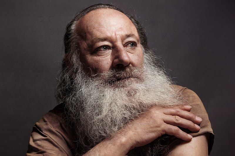 老人六十,七十,与与大微笑的一个长的胡子在黑暗的背景 免版税库存图片