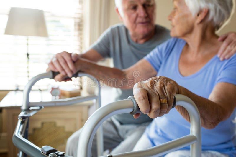 老人可安慰的妇女在卧室 免版税库存照片