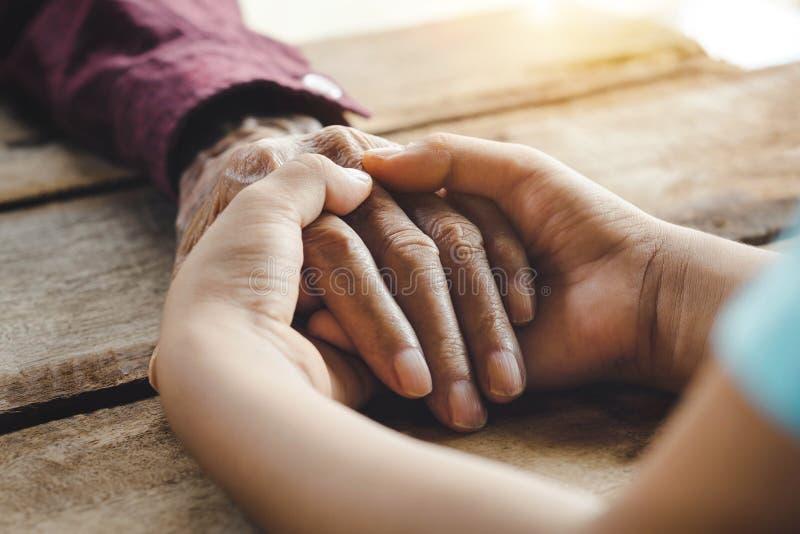老人和儿童` s手的手 免版税库存照片
