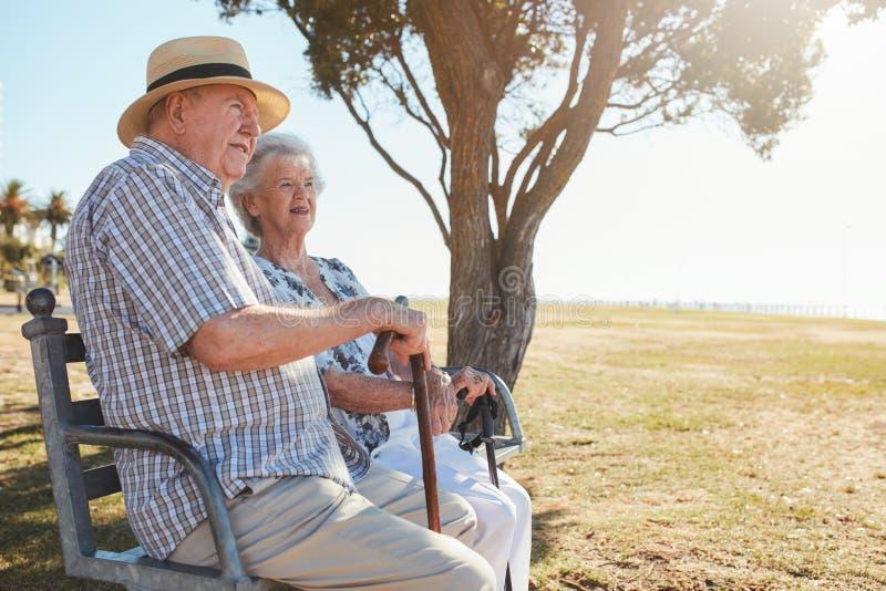 老人和妇女坐公园长椅户外 免版税库存图片