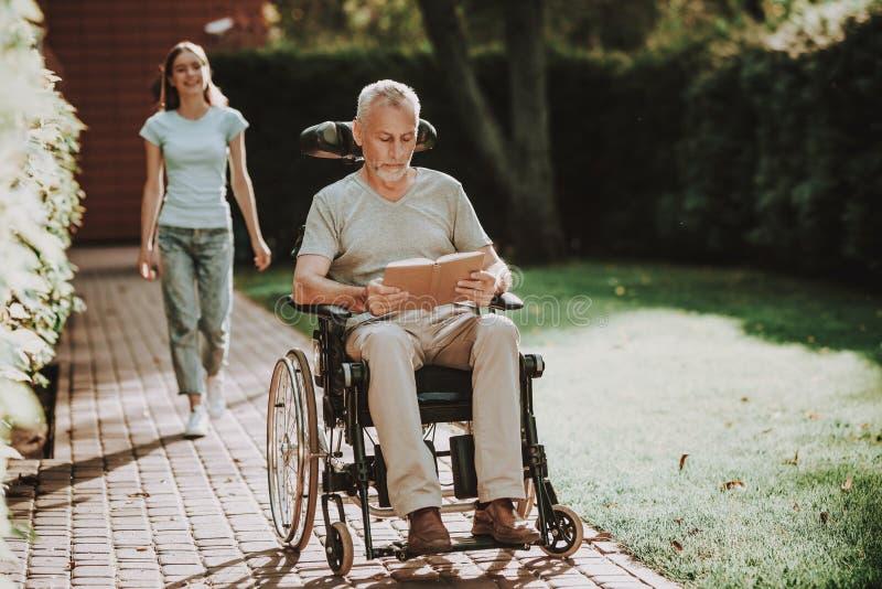 老人和护士一起走 变老和婴儿推车 库存图片