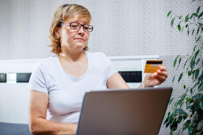 老人和现代技术概念 50s的画象成熟拿着信用卡的妇女手,使用网上互联网付款a 免版税库存照片