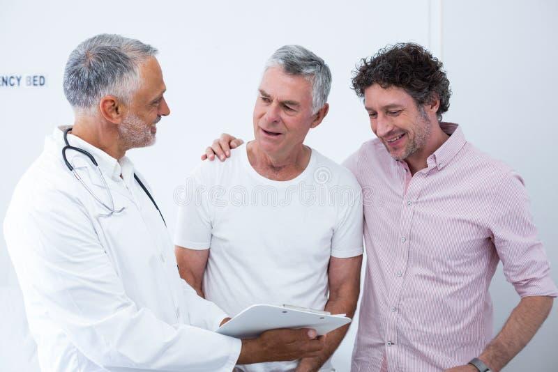 老人和他的监护人谈话与医生 图库摄影