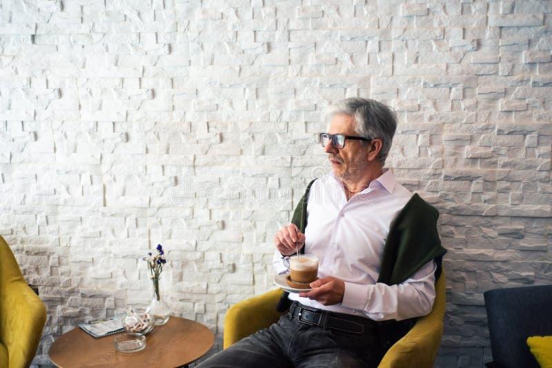 老人喝咖啡在酒吧 库存照片