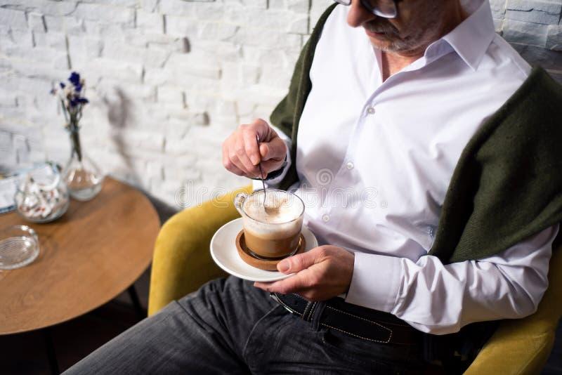 老人喝咖啡在酒吧 免版税库存照片