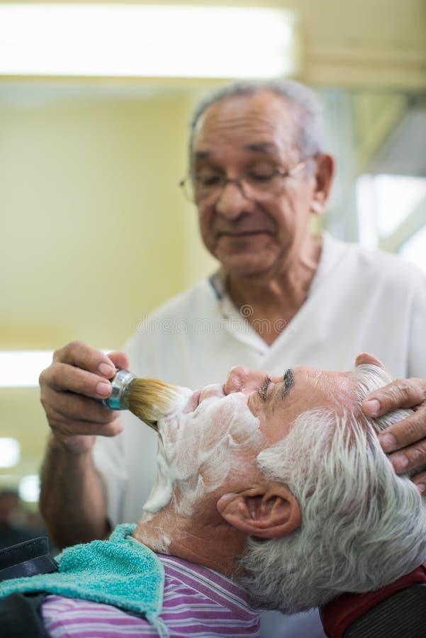 老人在作为刮客户的理发师的工作 库存照片
