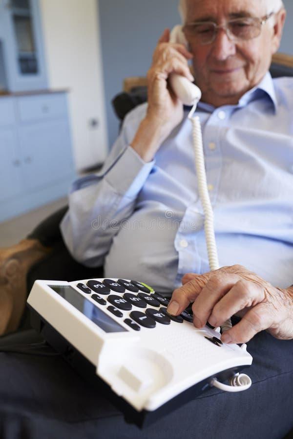 老人在家使用有结束大小的钥匙的电话 免版税库存图片