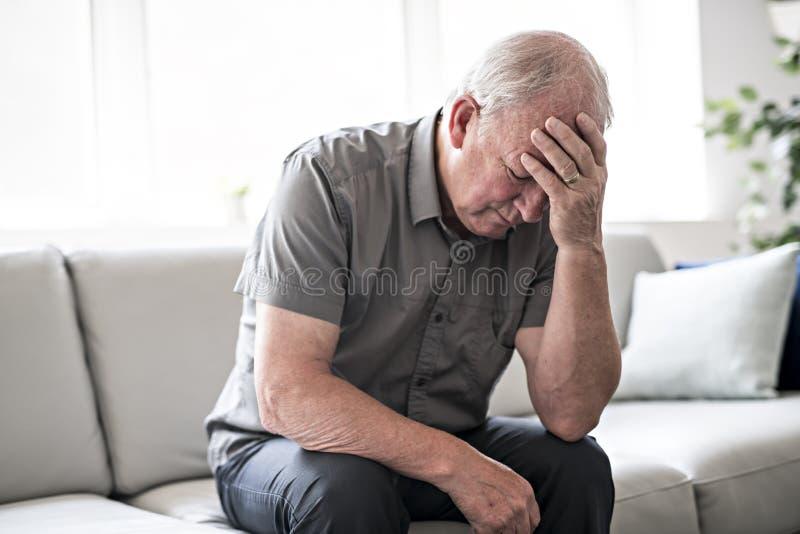 老人在家认为和坐沙发象哀伤 库存图片