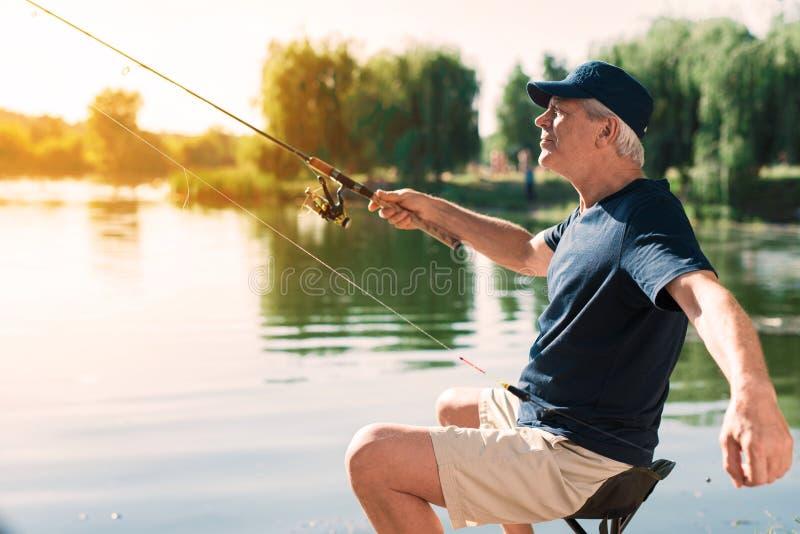老人在抒情诗钓鱼钩坐有一转动在他的手上和准备的河岸投掷 免版税库存图片