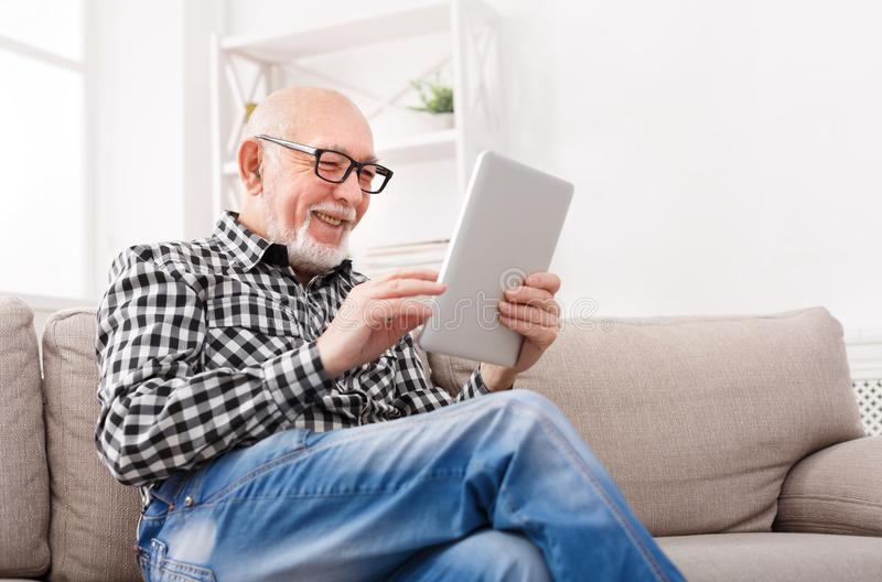 老人在数字式片剂的读书新闻 库存图片