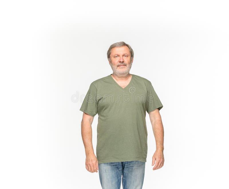 老人在白色背景隔绝的空的绿色T恤杉的` s身体特写镜头  嘲笑为设计观念 免版税库存照片