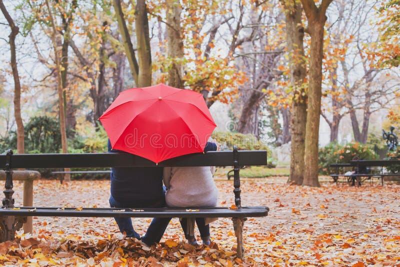 老人在秋天公园,爱概念退休了夫妇一起坐长凳 免版税库存图片