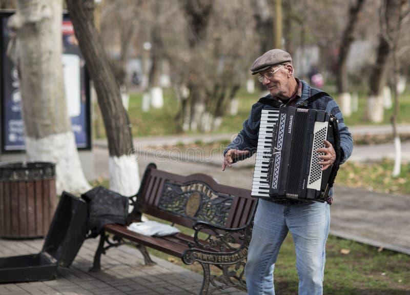 老人在耶烈万街道上的手风琴使用  的臂章 库存图片