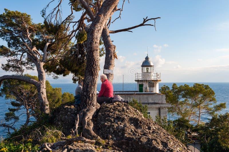老人坐一座石近的白色灯塔,位于菲诺港镇海岸线,意大利 免版税图库摄影