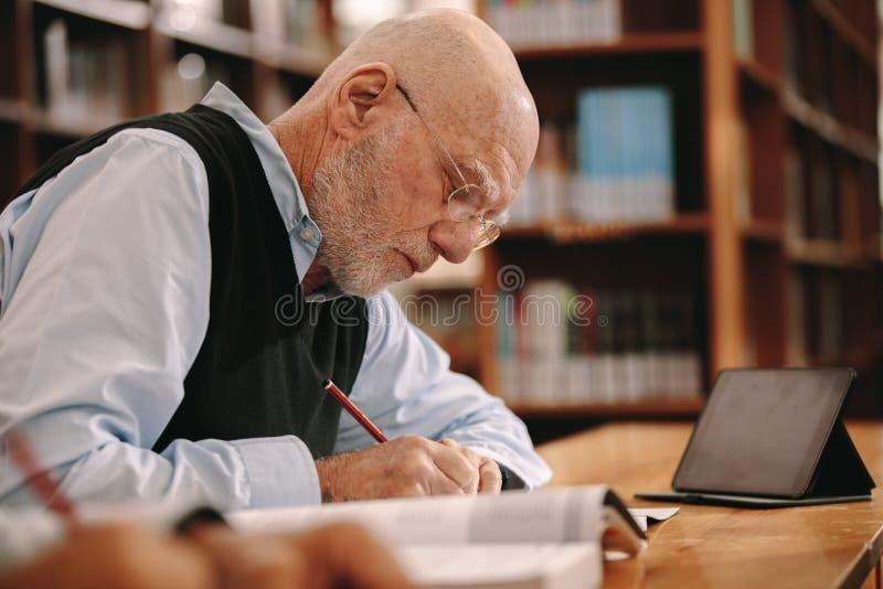 老人坐在教室的文字笔记 免版税图库摄影