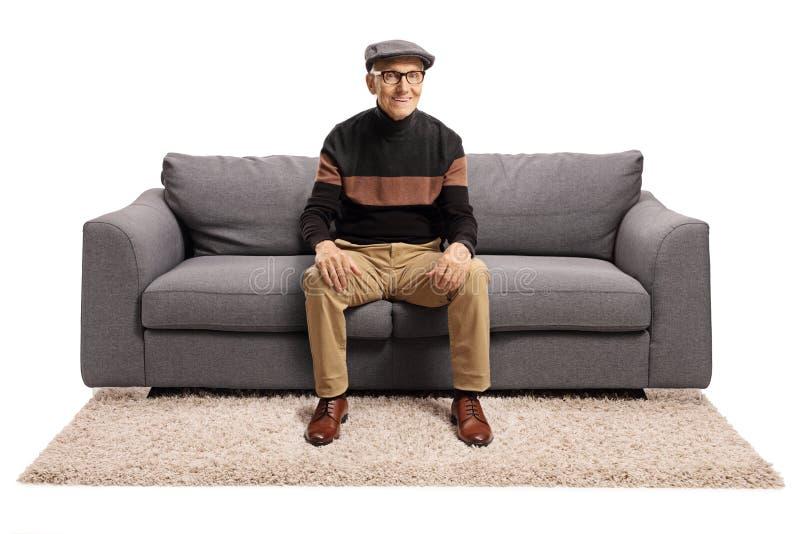 老人坐在沙发上微笑 库存照片