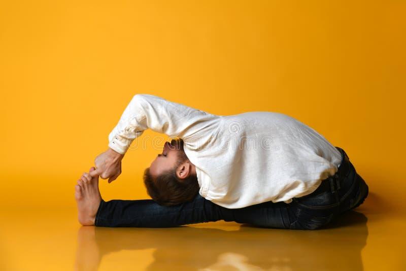 老人实践Ashtanga Vinyasa瑜伽后面弯曲的asana Paschimottanasana -供以座位的向前弯 免版税库存图片