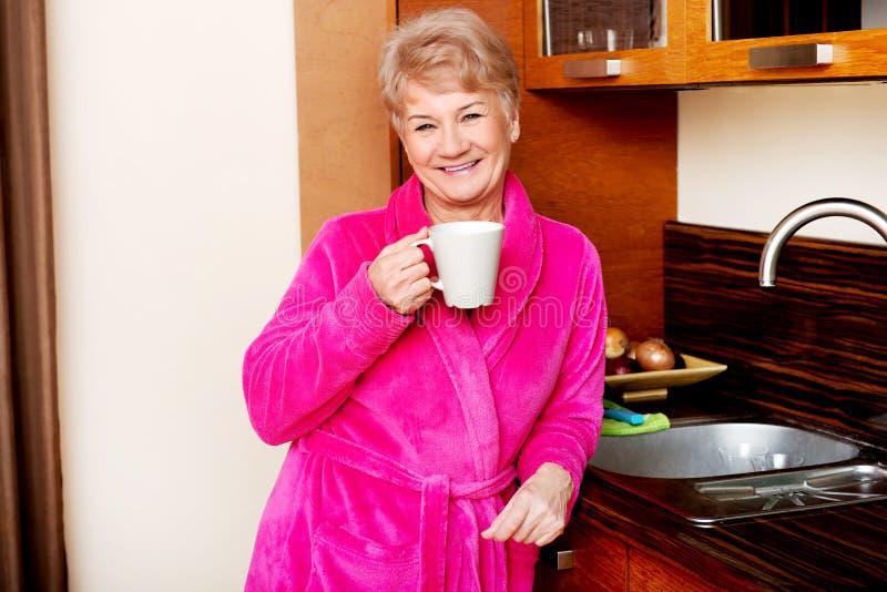 老人微笑妇女饮用的咖啡或茶在她的厨房里 免版税图库摄影