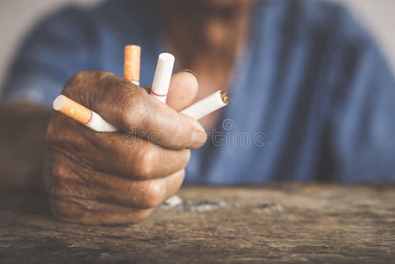 老人手毁坏的香烟中止抽烟的概念 免版税图库摄影