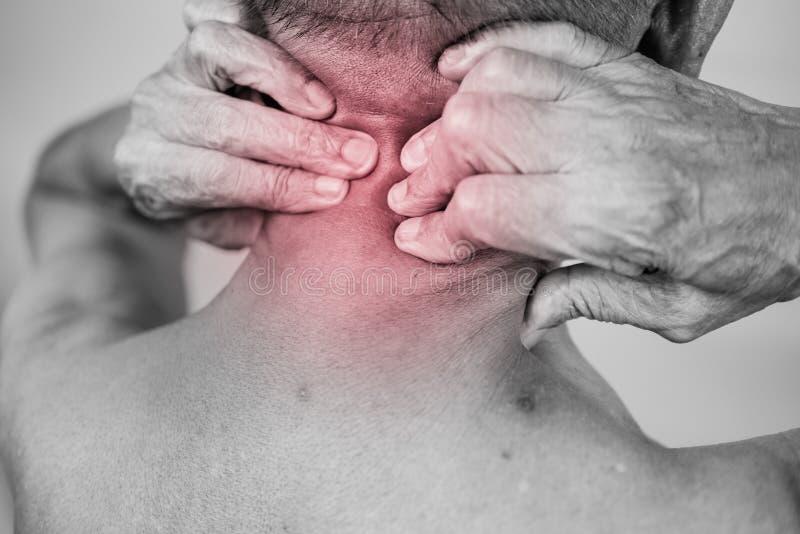老人手藏品他脖子和按摩在痛苦区域 clos 库存照片