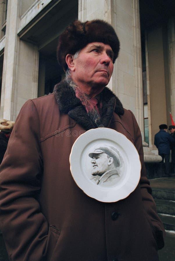 老人拿着有列宁画象的板材  免版税库存图片