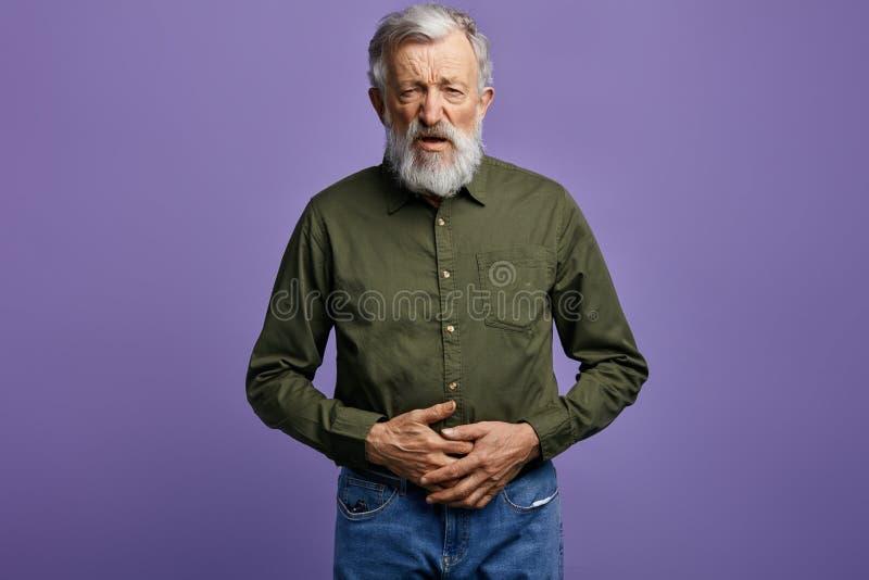 老人握他的胃,看看与凄惨的表示的照相机 免版税库存照片