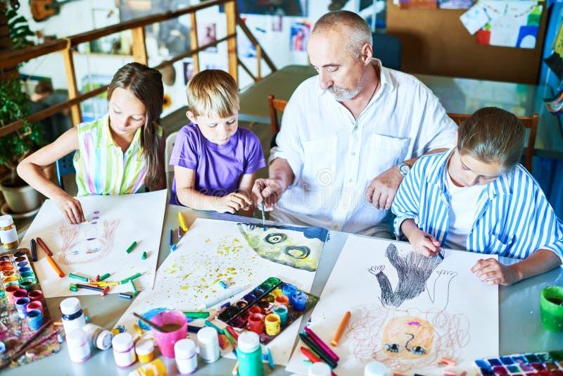 老人教的艺术课在学校 库存照片