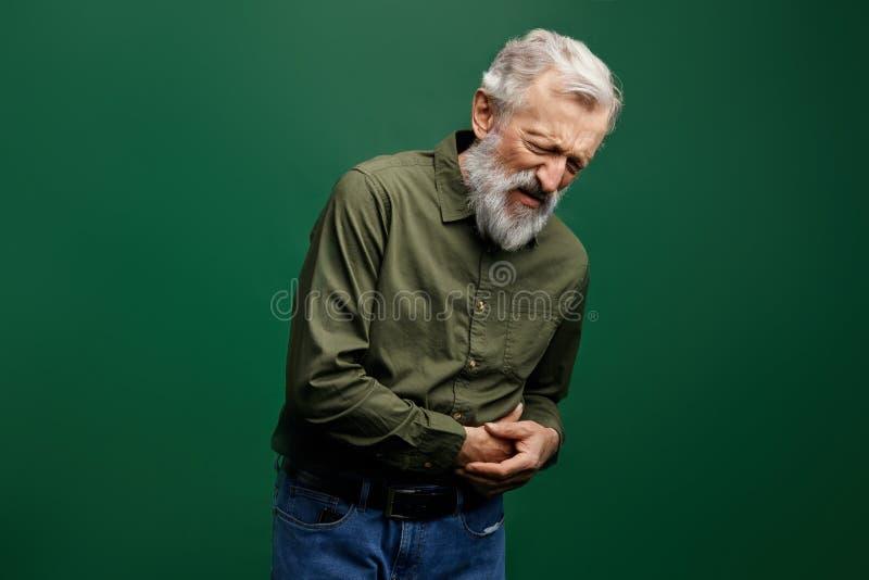 老人有stomachache 有接触他的胃的闭合的眼睛的老人 库存图片