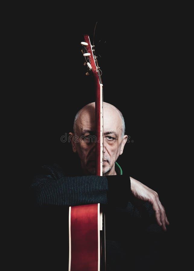 老人演播室画象有吉他的 免版税库存照片