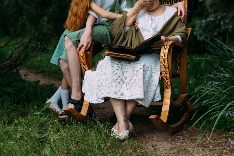 726成人金�yi*yf�_老人的记忆 参观祖母 有她的坐在一把摇椅的孙的祖母在庭院和watchi里