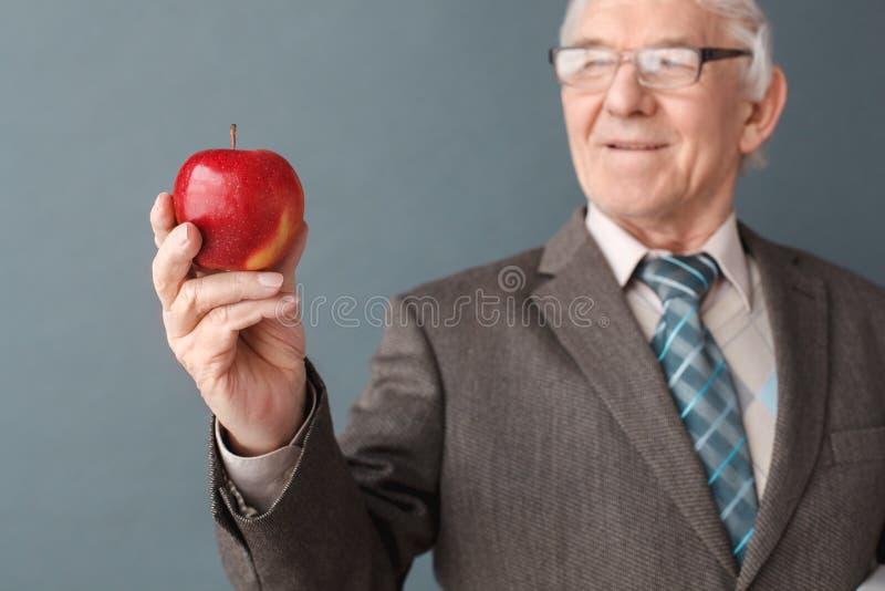 老人老师戴着眼镜在认为快乐的特写镜头的灰色看的苹果的演播室身分被弄脏 库存图片