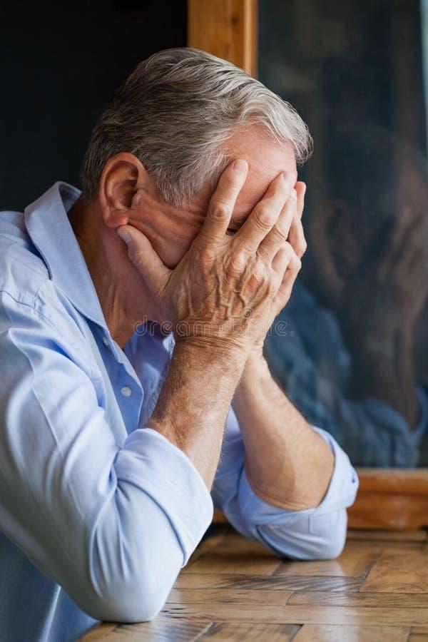 老人覆盖物面孔特写镜头,当坐在桌上时 免版税库存照片