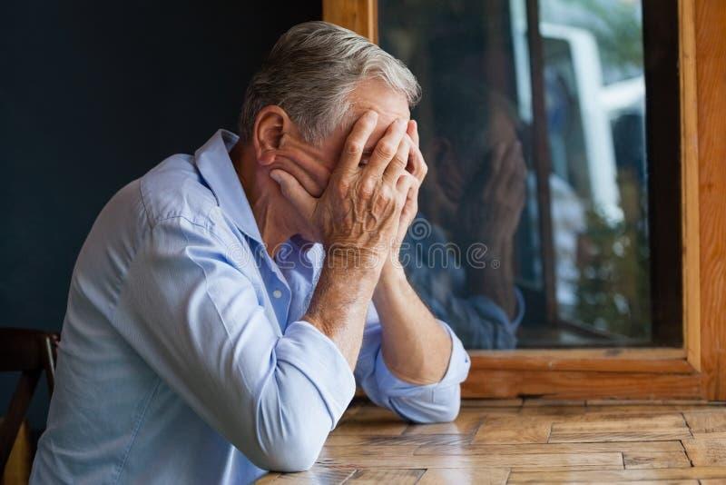 老人覆盖物面孔,当坐在桌上时 库存照片