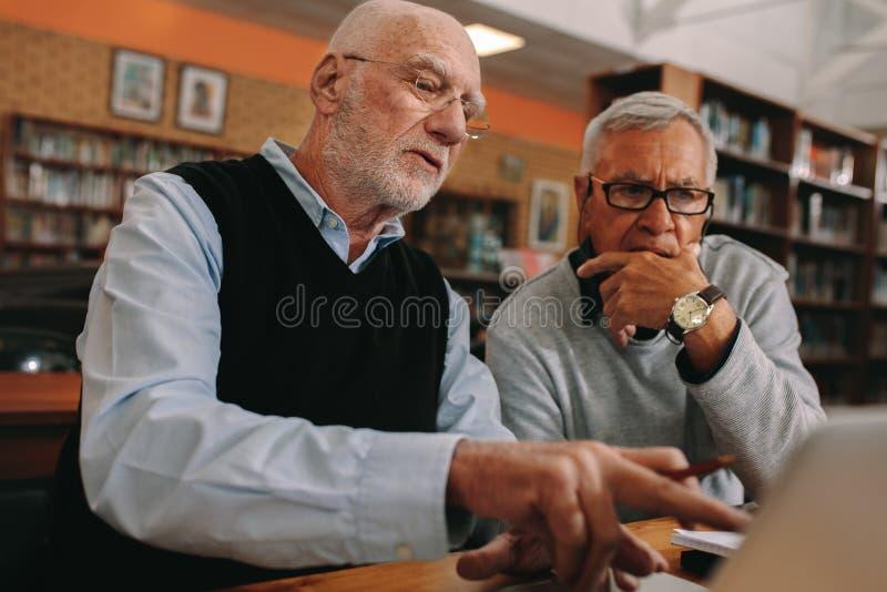 老人谈论坐的主题在图书馆 免版税库存图片