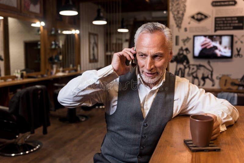 老人谈话在手机在酒吧柜台 库存图片