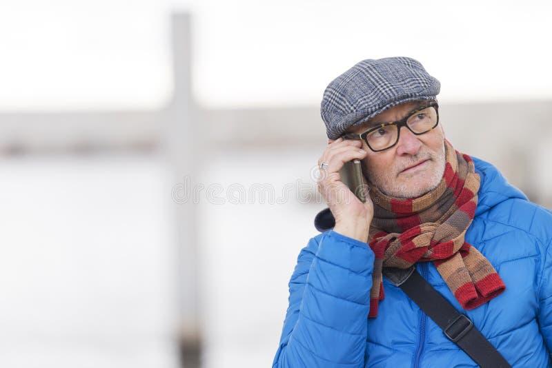 老人谈话在街道的手机 库存图片