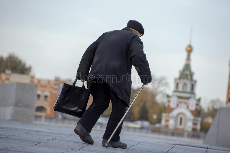 老人走与袋子 免版税图库摄影