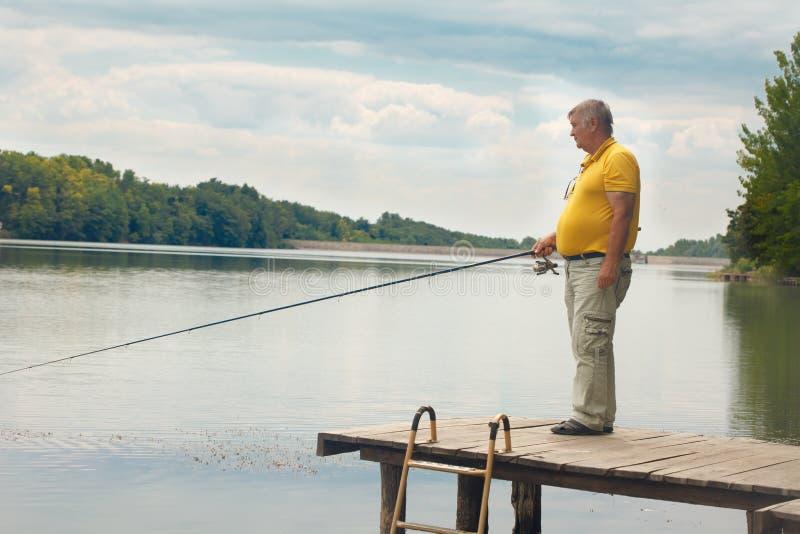 老人身分和渔在船坞 免版税库存图片