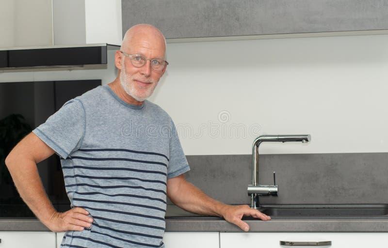 老人身分在厨房里 免版税图库摄影