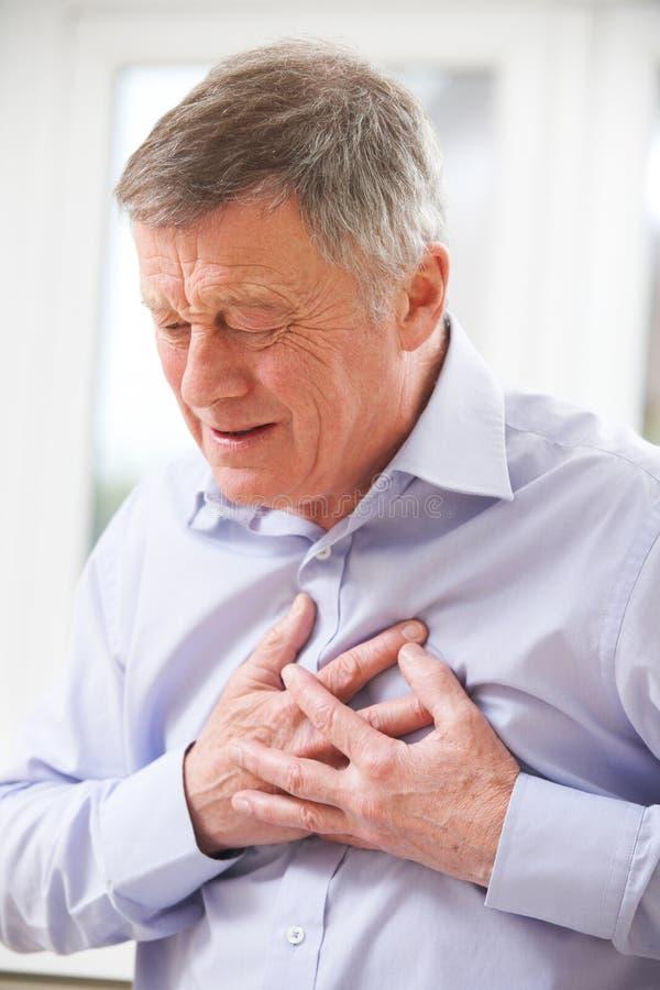 老人遭受的心脏病发作在家 免版税库存照片