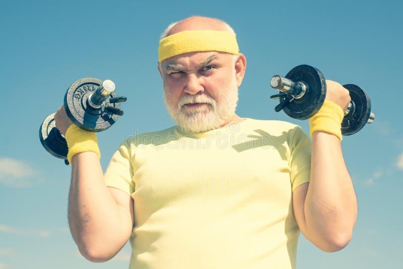 老人锻炼在康复中心 举的哑铃 老人健康俱乐部或康复中心年迈 免版税图库摄影