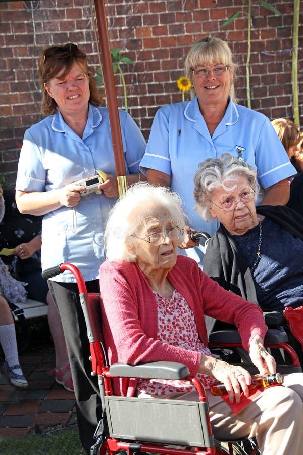 老人院居民和他们的护工 免版税图库摄影