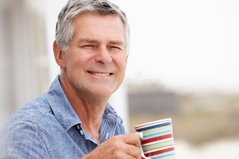 老人饮用的咖啡户外 免版税库存照片