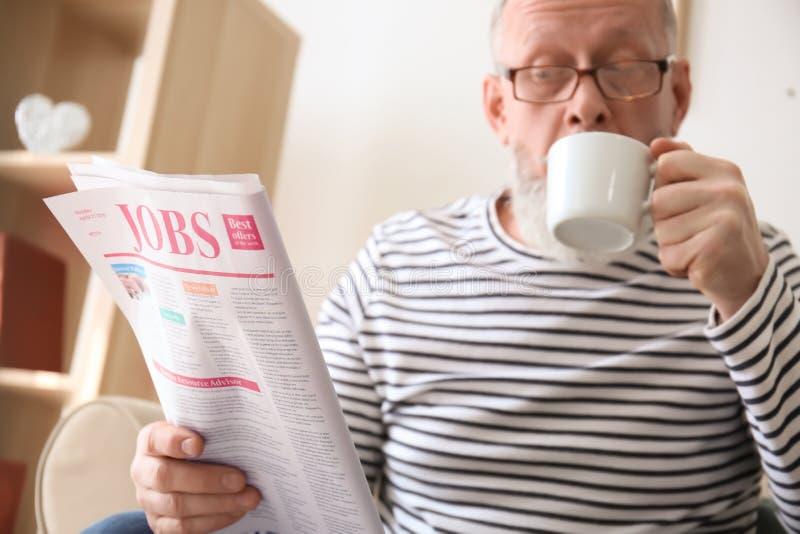 老人饮用的咖啡,当在家时读报纸 免版税库存图片