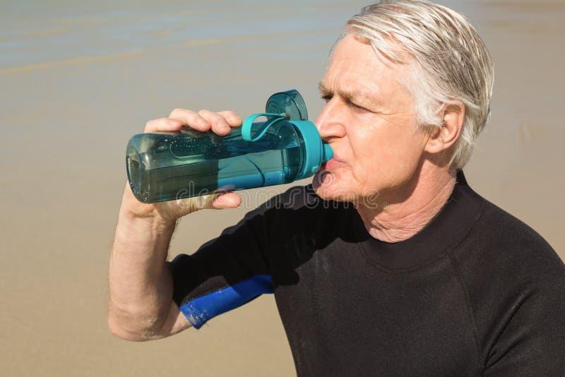 老人饮用水,当坐在海滩时 免版税库存照片