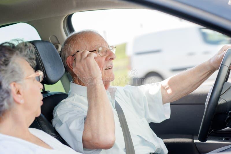 老人驾驶汽车和谈话在电话 免版税图库摄影