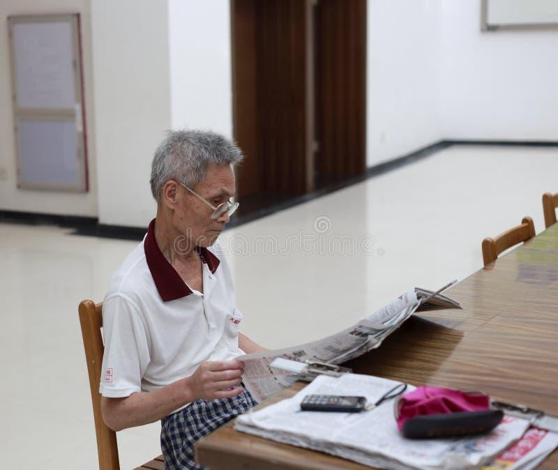 老人读书报纸在图书馆里 免版税图库摄影