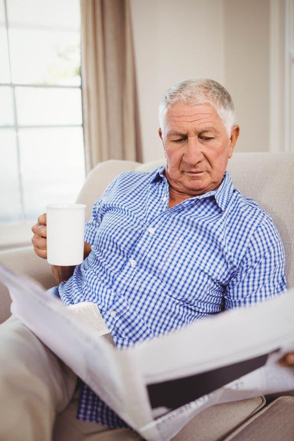 老人读书报纸在客厅 免版税库存照片