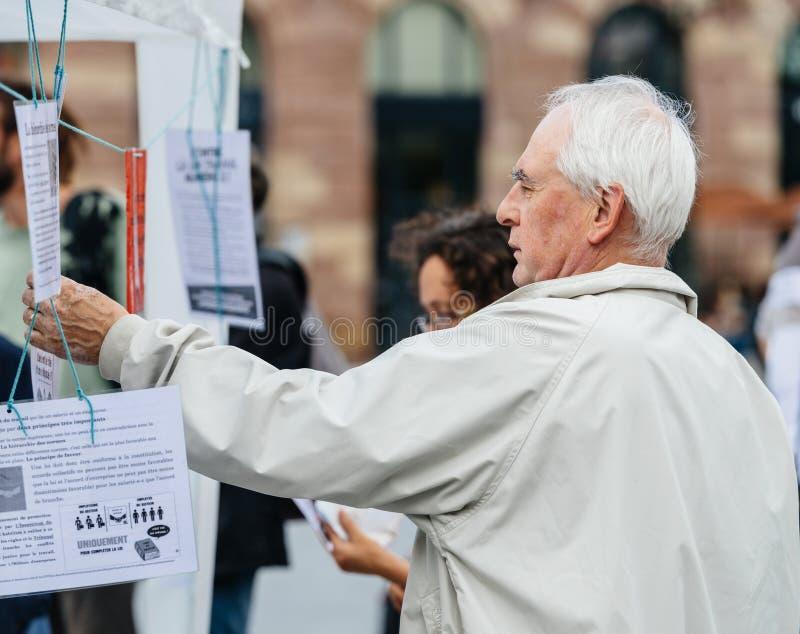 老人读书明显反对Macron 免版税图库摄影